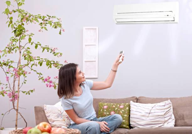 リモコンのエアコンを使用しての女性 - エアコン ストックフォトと画像