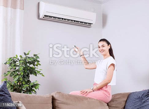 istock woman using remote control of air conditioner 1150347789