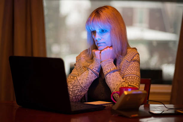 Woman Using Seasonal Affective Disorder (SAD) Light Middle-age woman with Seasonal affective disorder (SAD) working at home on computer with SAD LED light (lower right) which offers relief from seasonal depression. affective stock pictures, royalty-free photos & images