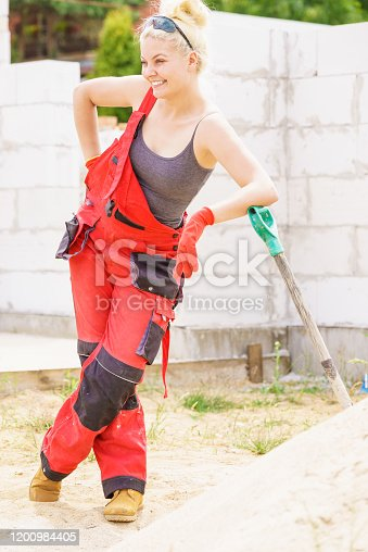 Woman working hard on construction site, holding shovel during break. Partially built new home early stage. Industry.