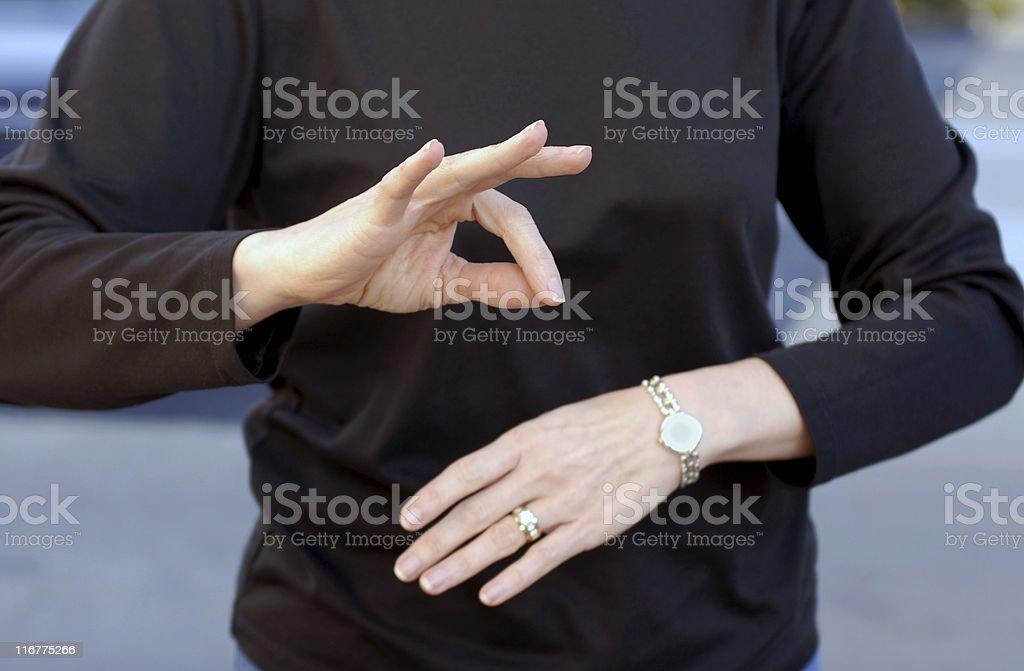 A woman using sign language wearing a black shirt stock photo