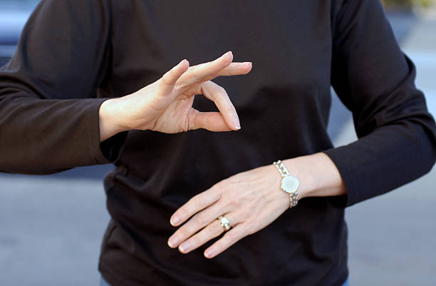 a woman using sign language wearing a black shirt - sign language stock photos and pictures