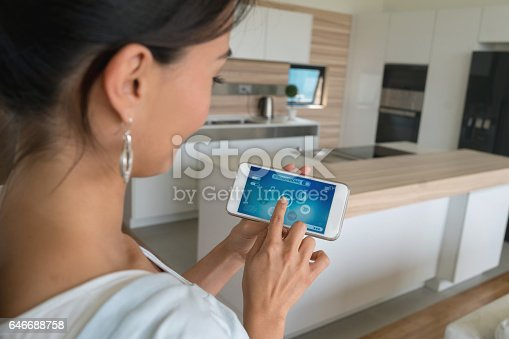 istock Woman using smart home app on her cell phone 646688758
