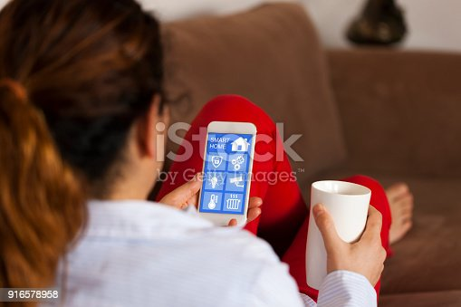 1158812288istockphoto Woman using smart home app on her cell phone 916578958