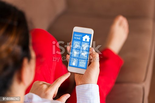 1158812288istockphoto Woman using smart home app on her cell phone 916586242