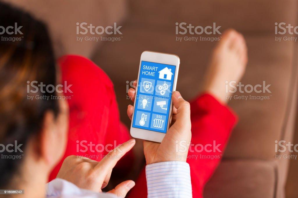 Frau mit smart home-app auf ihrem Handy – Foto