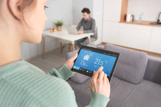 Woman using smart home application on tablet. stock photo