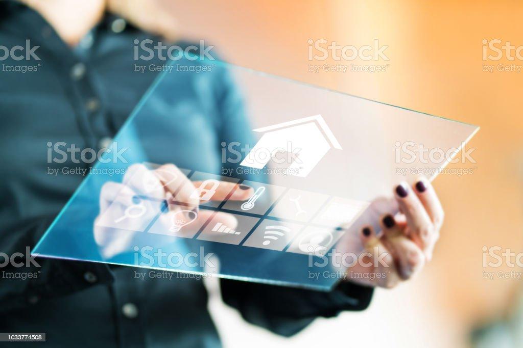Mujer con aplicación de control de casa inteligente con tabletas de cristal transparente futurista. Dedo tocando el botón a la propiedad de control con tecnología digital automatizada, AI y IOT. - foto de stock