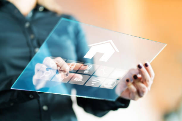 Woman using smart home control application with futuristic transparent glass tablet. Finger touching button to control property with automated digital technology, AI and IOT. stock photo