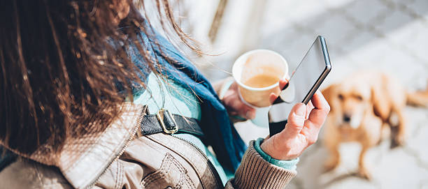 Woman using smart phone and holding coffee stock photo