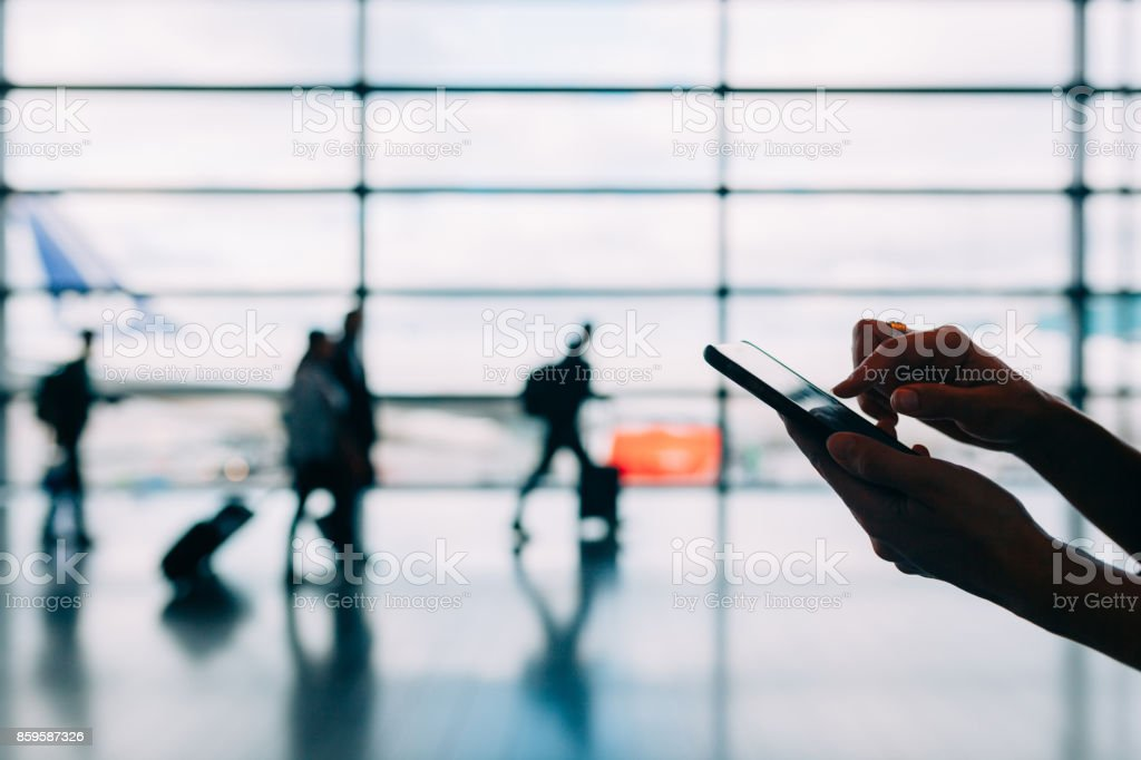 Woman Using Smart Phone at Airport stock photo