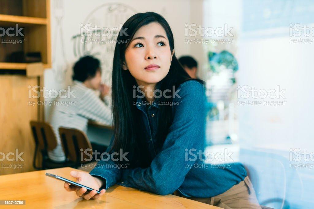 女性がカフェでスマート フォンを使用して ストックフォト