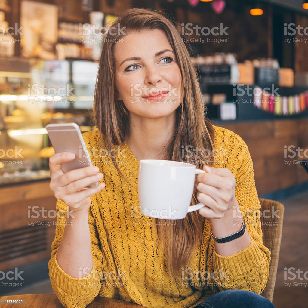 Woman using smart phone at coffee shop. stock photo