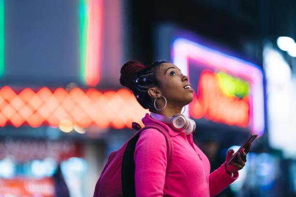 frau benutzt smartphone nachts - neontasche stock-fotos und bilder