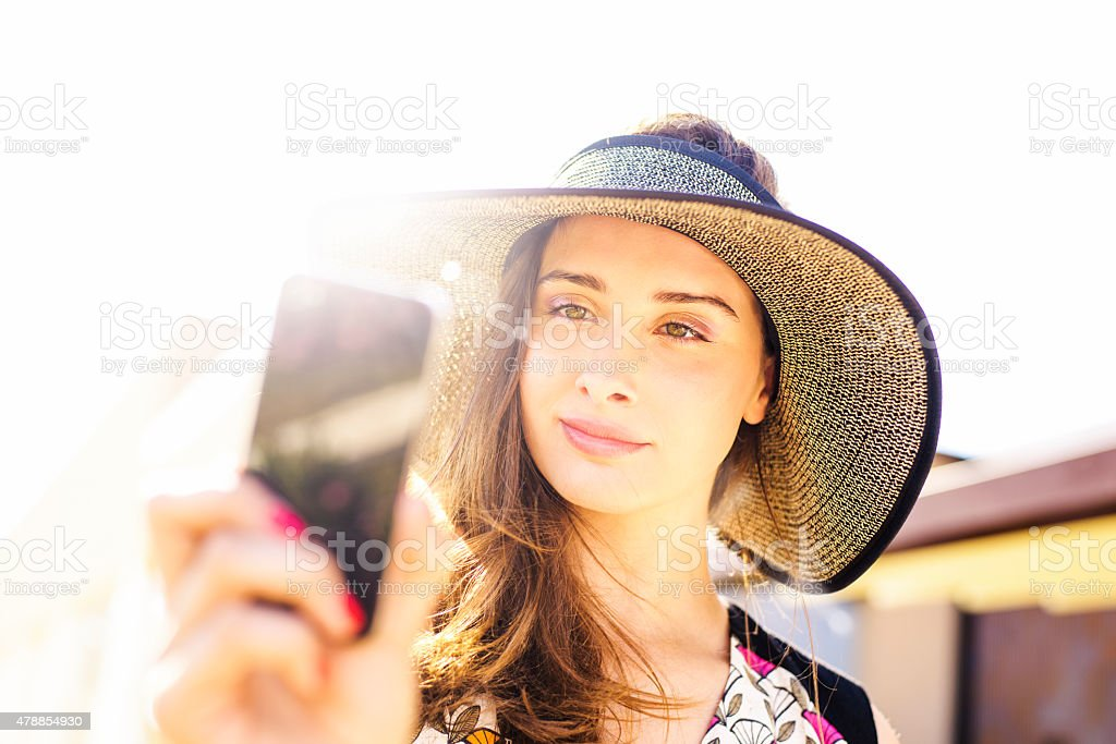Woman Using Smart Phone For Video Call or Photo Outdoors royalty-free stock photo
