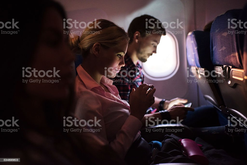 Woman using smart phone in airplane. stock photo
