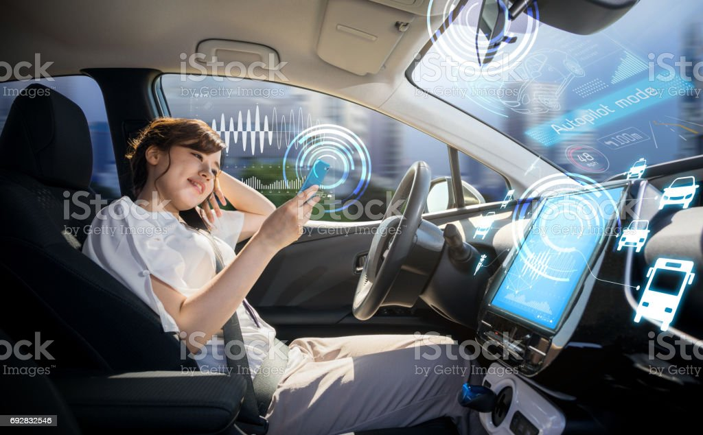woman using smart phone in autonomous car. self driving vehicle. autopilot. automotive technology. - foto stock