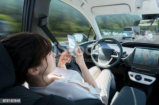 istock woman using smart phone in autonomous car. self driving vehicle. autopilot. automotive technology. 829192848