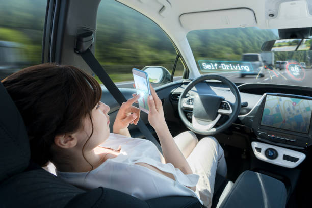 woman using smart phone in autonomous car. self driving vehicle. autopilot. automotive technology. stock photo