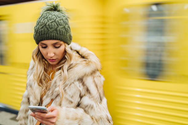 Woman using smart phone in subway Young woman using train as transportation central europe stock pictures, royalty-free photos & images