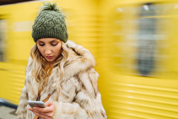 femme utilisant le téléphone intelligent dans le métro - europe centrale photos et images de collection