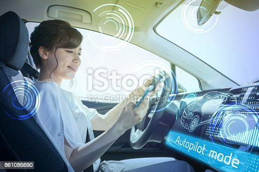 istock woman using smart phone in the car. autonomous car. self driving vehicle. autopilot. automotive technology. 861086690