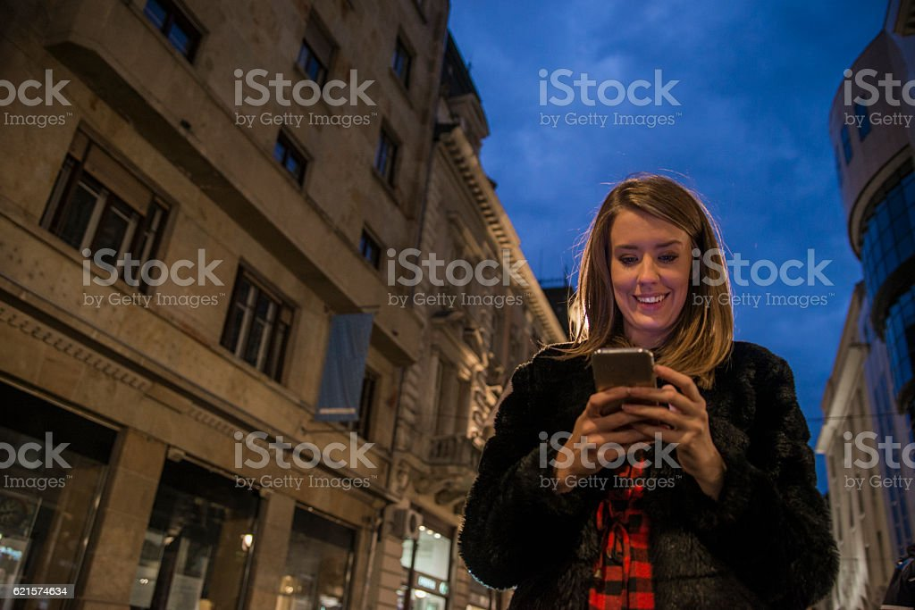 Woman using smart phone mobile in the city at night photo libre de droits