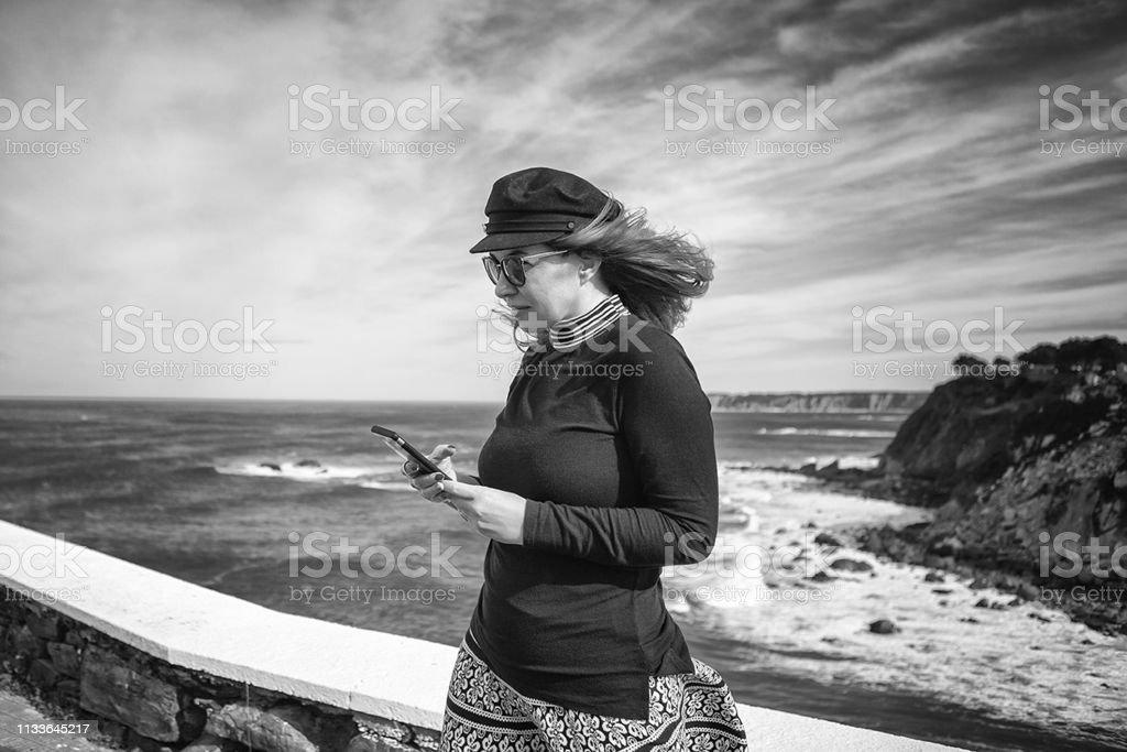 Woman using smart phone near the sea. Black and white photo