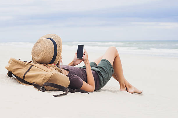 Woman using smart phone on a beach stock photo