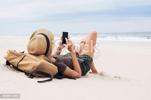 istock Woman using smart phone on a beach 625874352