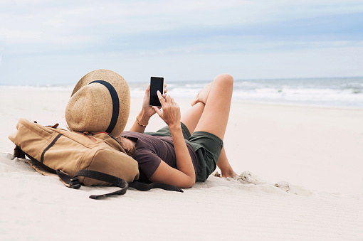 Woman using smart phone on a beach