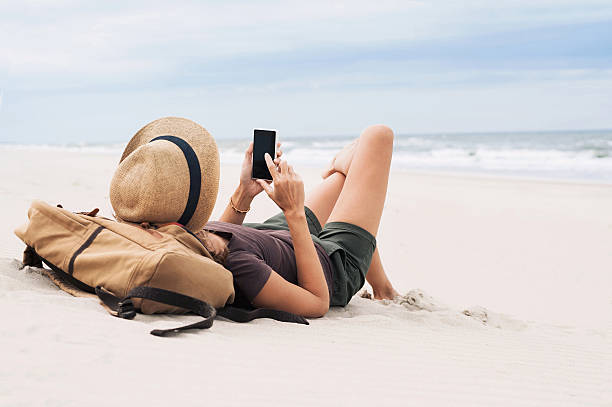 Woman using smart phone on a beach stock photo