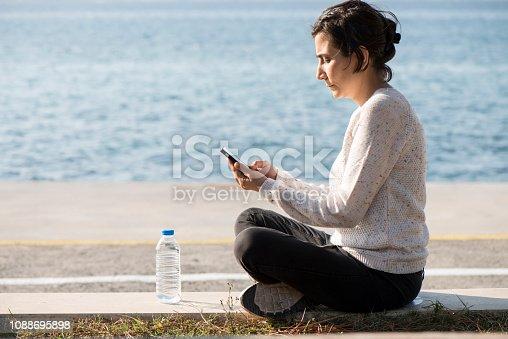 istock Woman Using Smart Phone On Beach 1088695898