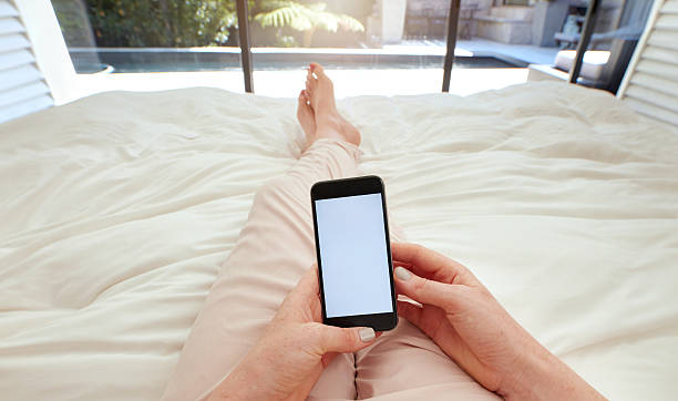 Woman using smart phone on bed stock photo