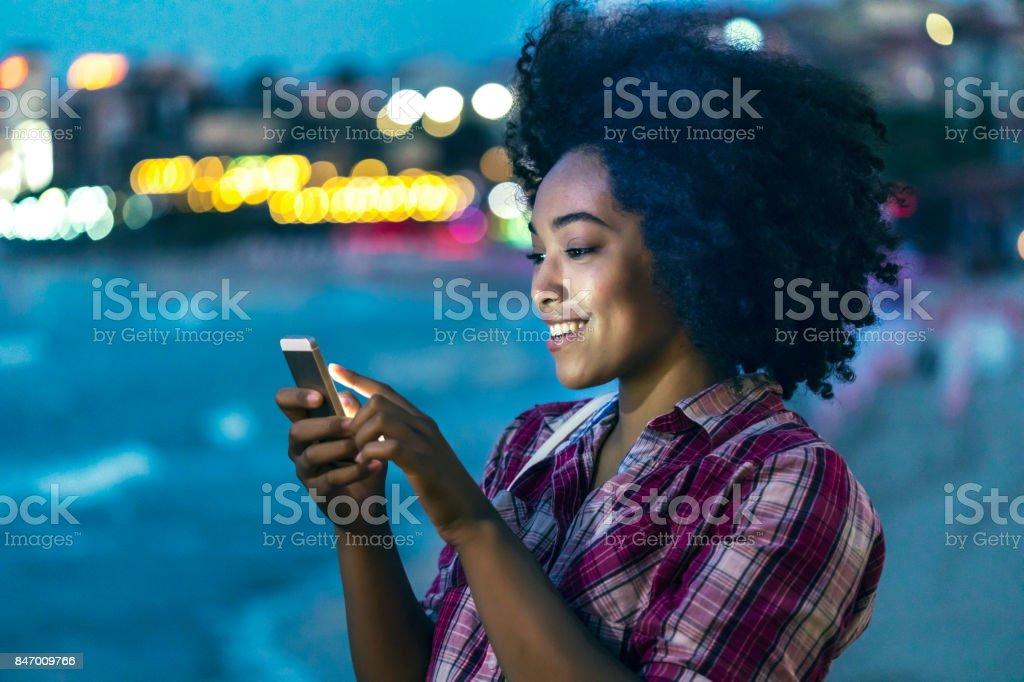 Woman using smart phone on street at night stock photo