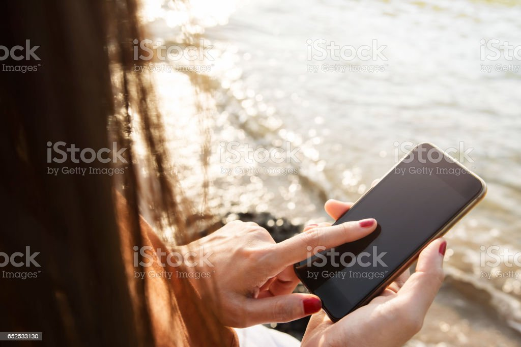 Woman using Smart Phone on summer Beach stock photo