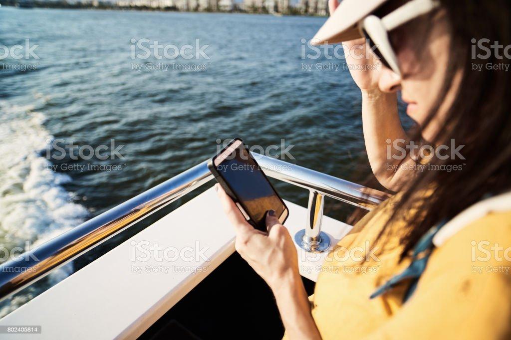 Frau mittels Smartphone auf der Fähre – Foto