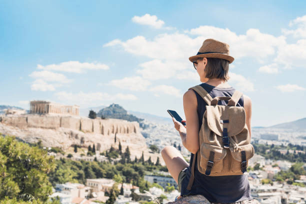 Woman using smart phone on vacations in Athens Young woman traveler using mobile phone outdoor travel stock pictures, royalty-free photos & images