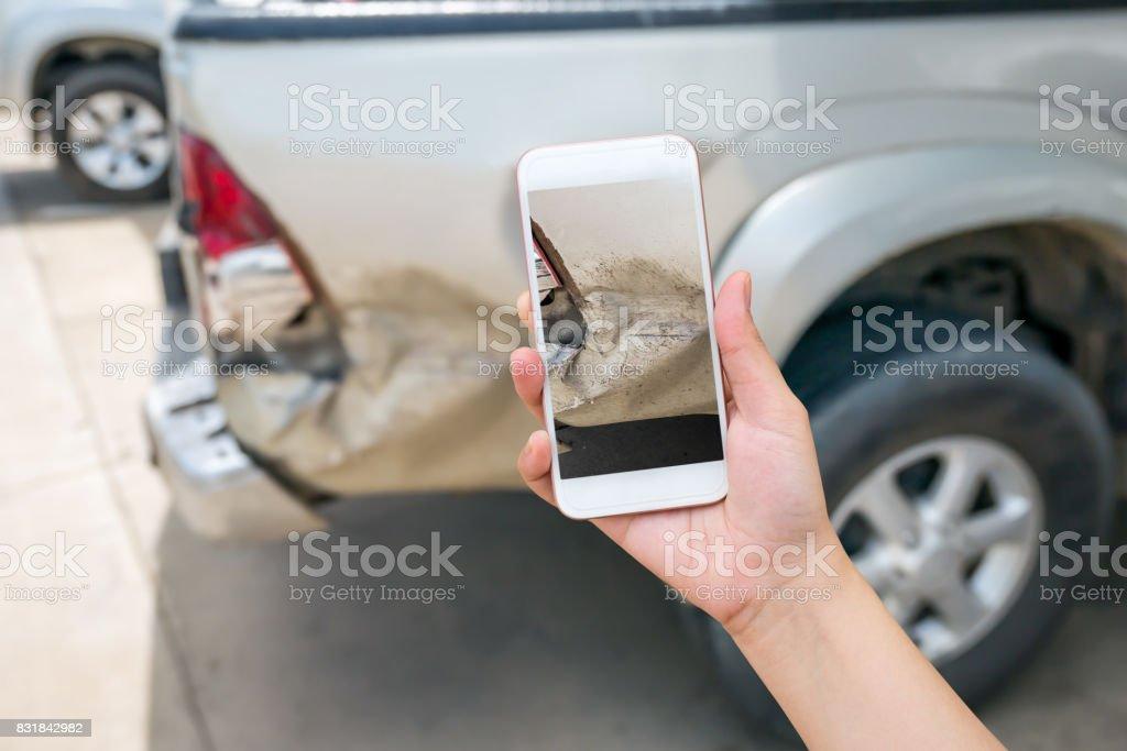 woman using smart phone to take car damage photo stock photo