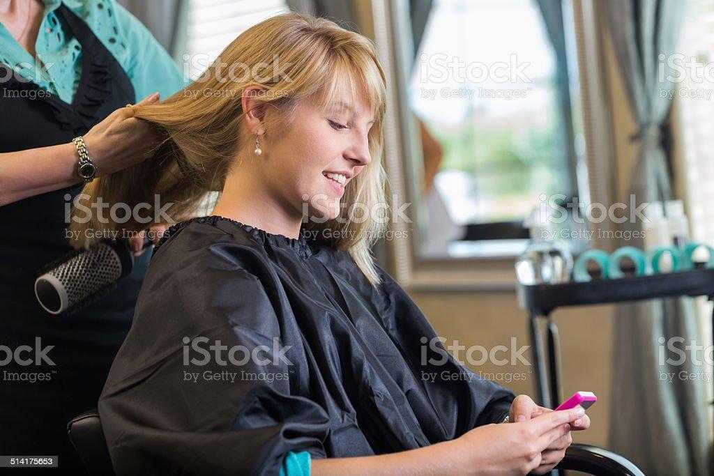 Mujer usando teléfono inteligente mientras hairstylist cortes de cabello rubia - foto de stock