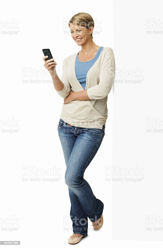 Woman Using Smart Phone While Leaning On Billboard stock photo