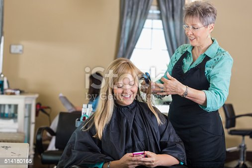 istock Woman using smart phone while professional stylist straightens hair 514180165