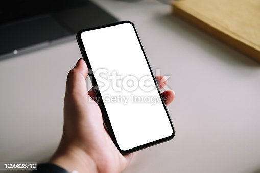 Woman using smart phone with blank screen mock up on workplace desk