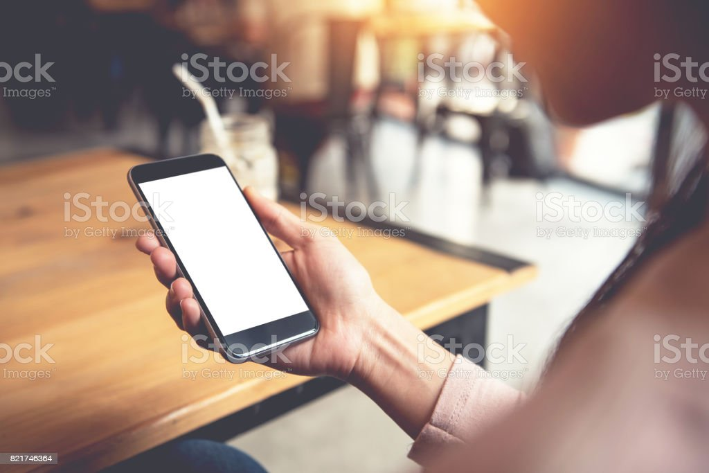 Woman using smart phone with white screen in cafe.