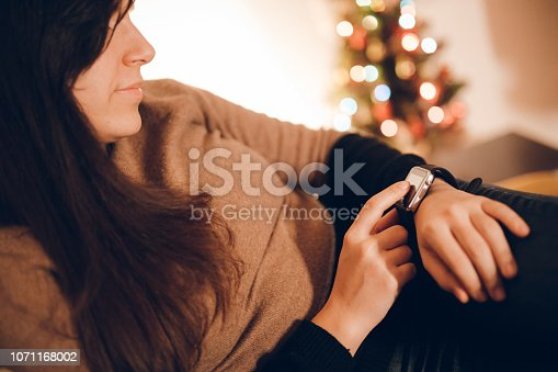 istock Woman using smart watch at home 1071168002