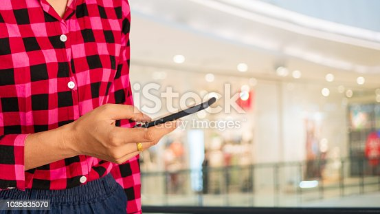 613672992 istock photo Woman using smartphone and finger touching with on the shopping mall background.Customers can order things from via internet,online shopping and Payment. 1035835070