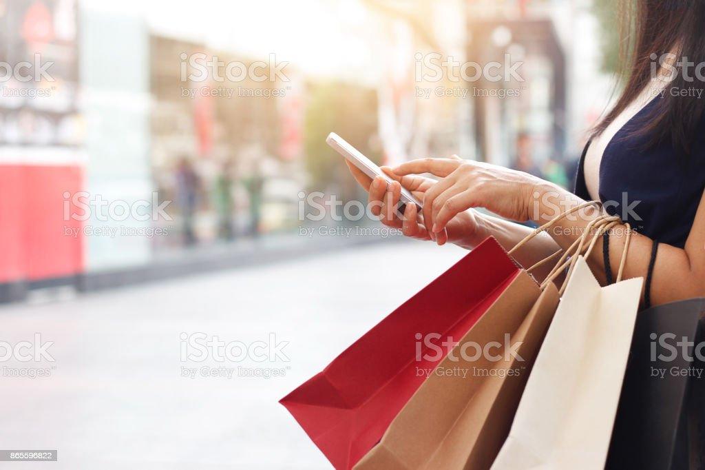 Mujer con smartphone y sosteniendo la bolsa estando en el fondo del centro comercial - foto de stock