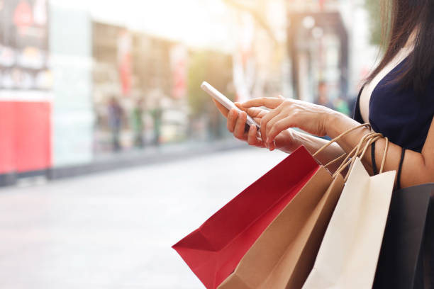 woman using smartphone and holding shopping bag while standing on the mall background - shopping stock photos and pictures