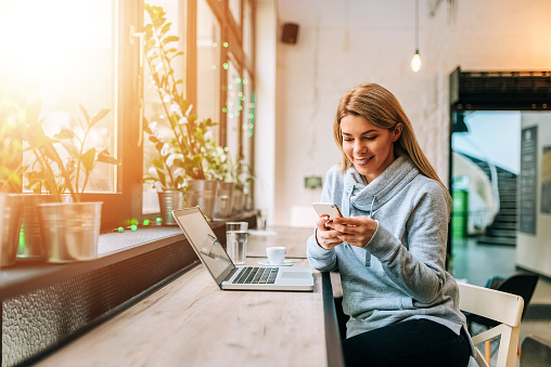Woman using smartphone and laptop at a lovely bright cafe.