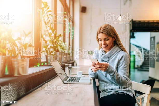 Woman using smartphone and laptop at a lovely bright cafe picture id945746492?b=1&k=6&m=945746492&s=612x612&h=8lemoslywwg3t7oehzskcmj9v0o0moml6hc7vu agq0=